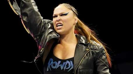 Ronda Rousey holds up the belt after defeating