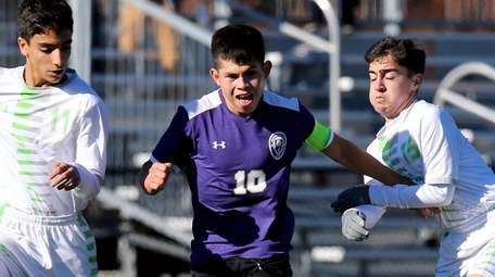 Greenport's William Chapeton splits two Solomon-Schecter defenders, and