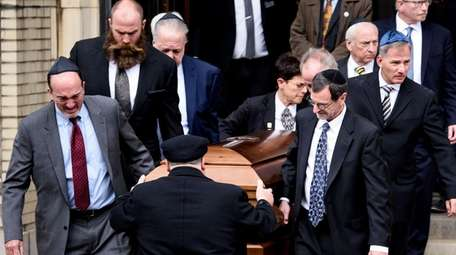 Pallbearers carry a casket from Rodef Shalom Congregation