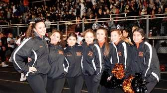 H. Frank Carey High School varsity cheerleaders hang