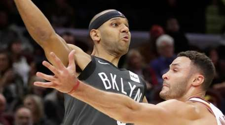 The Nets' Jared Dudley passes over the Cavaliers'