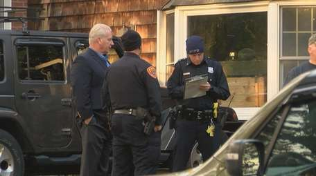 Investigators confer outside the Carrolls' Olive Street home