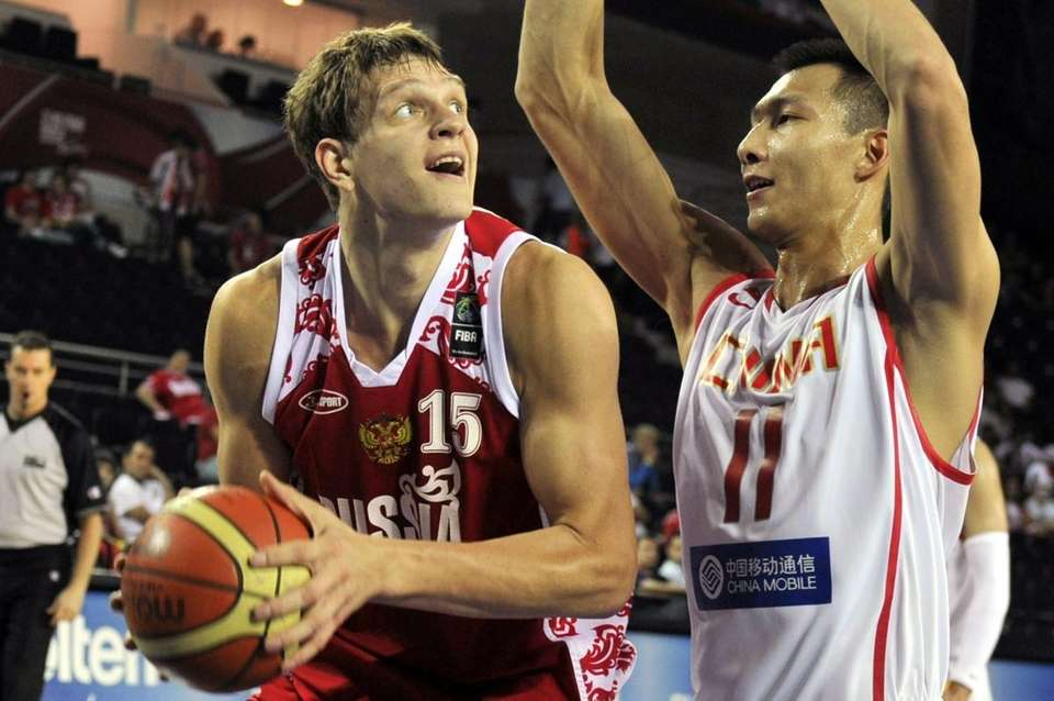 Russia's Timofey Mozgov, left, is defended by China's