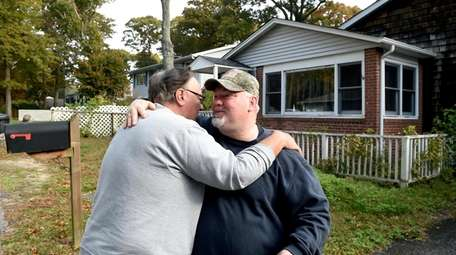 Mike Carroll, right, is hugged by friend Tony