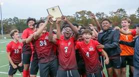 Amityville celebrates with the winners plaque after their