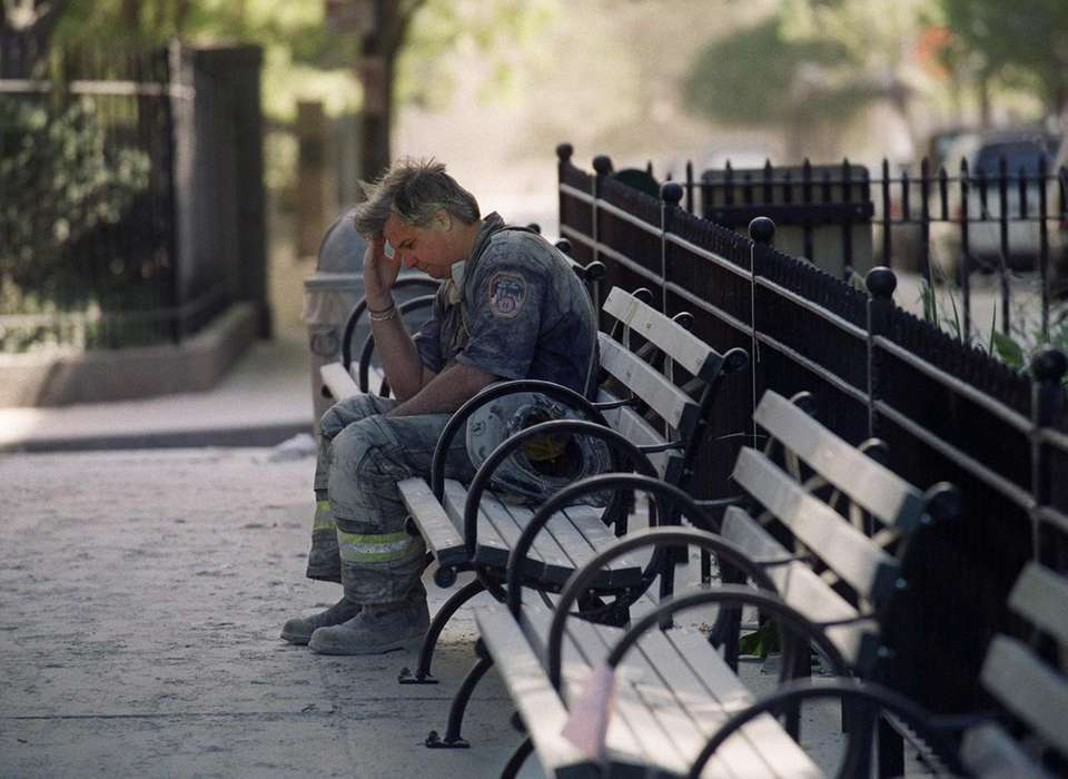 A firefighter pauses on a bench as he