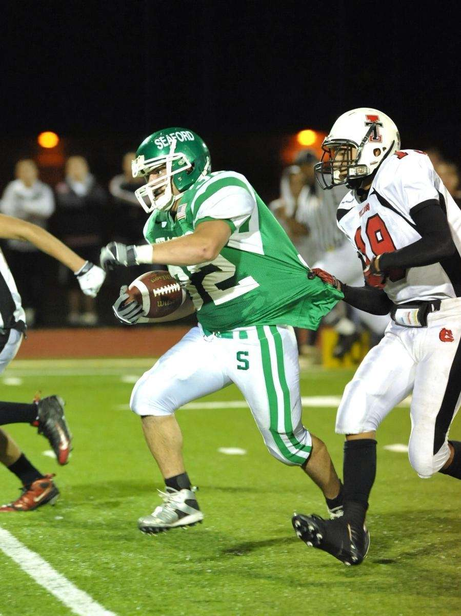Seaford's RB, Justin Buckley (32, left), fights for
