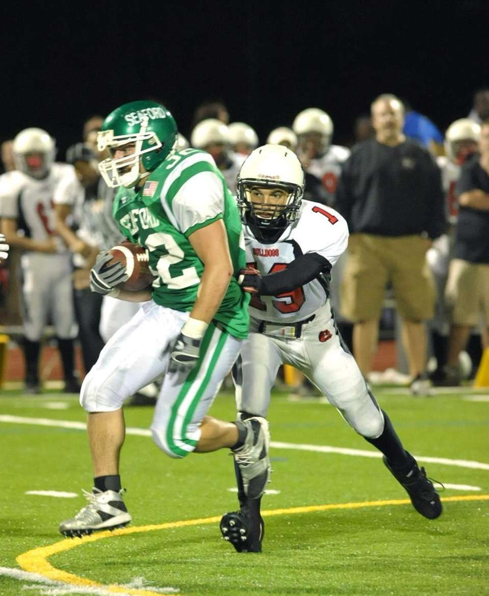 Seaford's RB, Justin Buckley (32, left), goes airborn