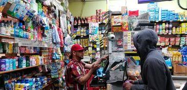 West Harlem Deli co-owner Jose Espinosa, left, waits