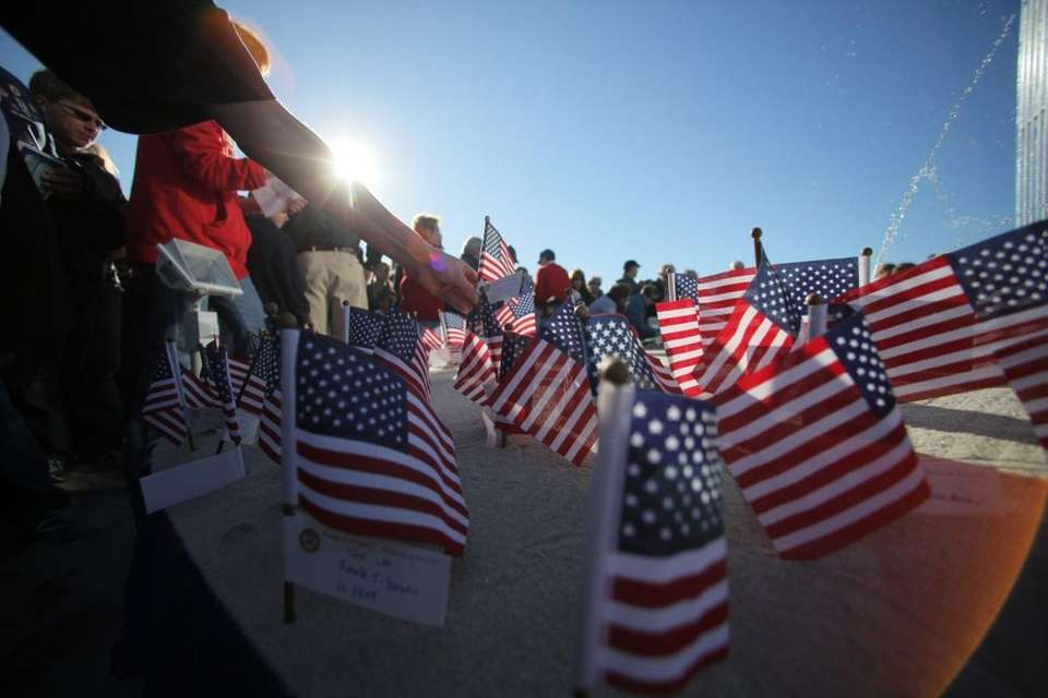 People place flags at a memorial after a