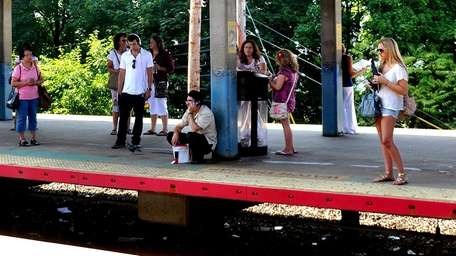 Passengers wait for a westbound LIRR train at