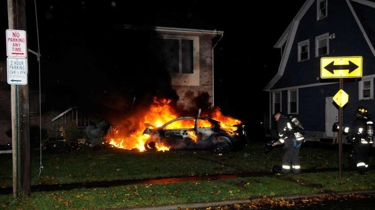 The car in flames on the lawn of