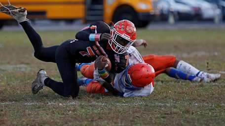 Jovani Duran #81 of Malverne tackles Jarell Brown