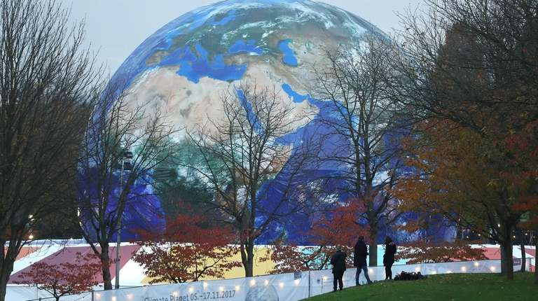 "People walk past the ""Climate Planet,"" an exhibition"