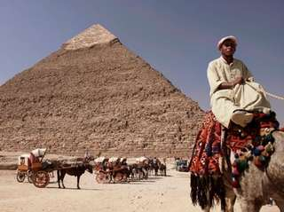 Egyptian camel driver waits for customers outside the