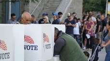 Voters mark their ballots at an early voting