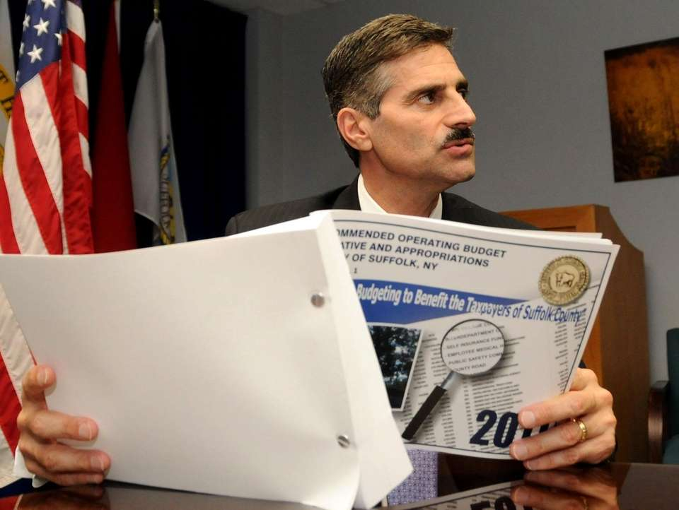 Suffolk County Executive Steve Levy holds a copy