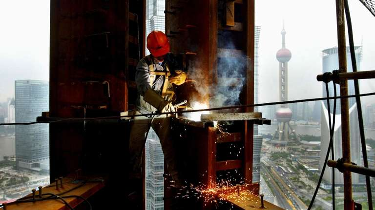 A worker welds on the Shanghai Global Financial