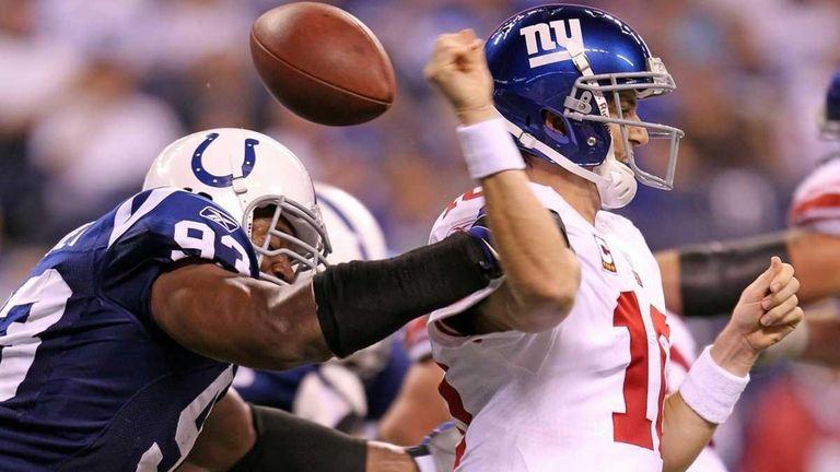 Indianapolis' Dwight Freeney hits Giants quarterback Eli Manning