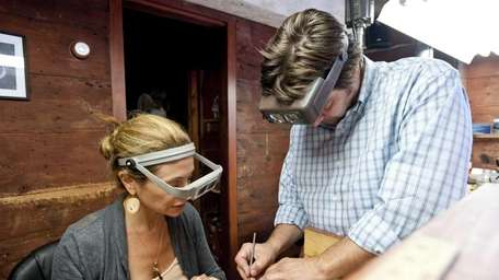 Jewelrymaker Eric Messin, right, helps student Amanda Grove