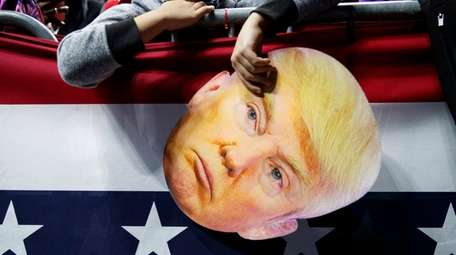 James Crockett, 10, holds a mask of President