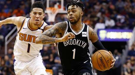 Nets guard D'Angelo Russell, right, drives past Suns