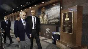 Yogi Berra, front left, and Reggie Jackson walk