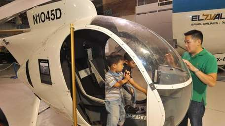 A father and his sons explore a helicopter