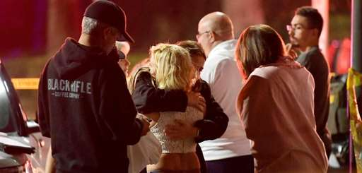 People comfort each other Thursday near the scene
