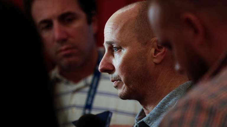 Yankees general manager Brian Cashman, center, speaks to