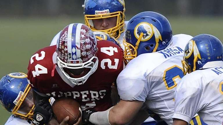 Comsewogue's defense takes down Bellport's Travis Houpe during