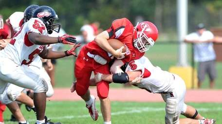 East Islip quarterback Kevin Hutchinson is tackled by