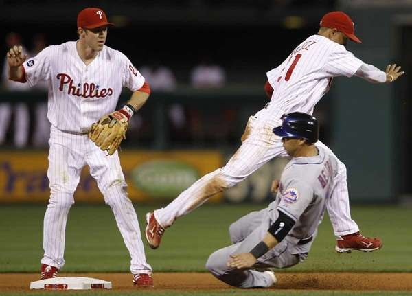 Philadelphia Phillies shortstop Wilson Valdez, top right, leaps