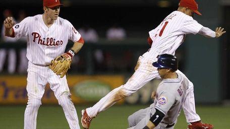 Philadelphia Phillies shortstop Wilson Valdez, top right, leaps