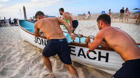 Lifeguards work to bring up a life boat
