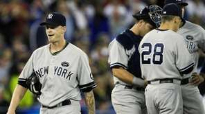 Yankees starting pitcher A.J. Burnett, left, walks back