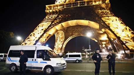 Police officers stand in front of the Eiffel