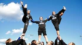Centereach cheerleaders perform during a football game against