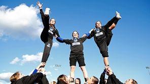 Centereach cheerleaders perform during a football game against