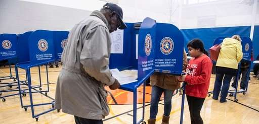 Voters mark their ballots at Roosevelt High School