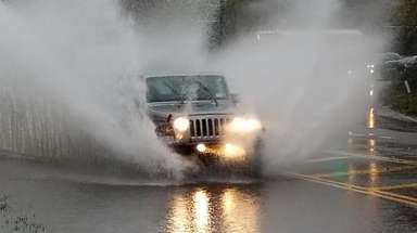 A Jeep plows through a flooded portion of