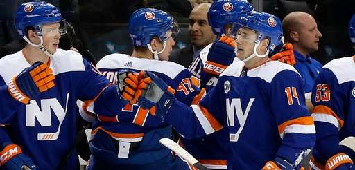 The Islanders' Tom Kuhnhackl, right, celebrates his third-period