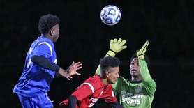 Connetquot's Emmanuel Kwansah, in blue, hits the ball