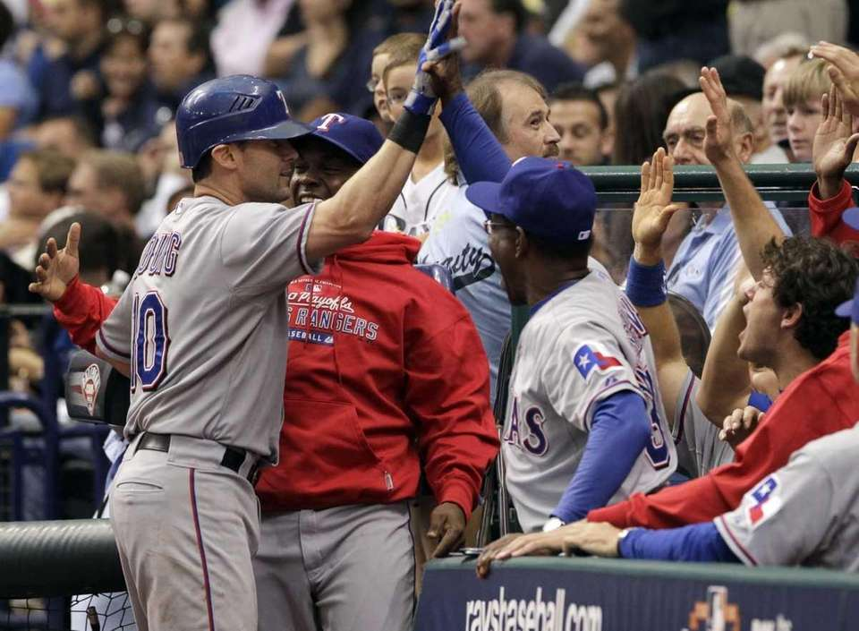 Texas Rangers' Michael Young is congratulated by teammates,