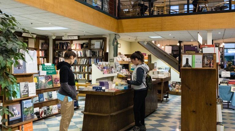 Customer looks through racks of books for sale