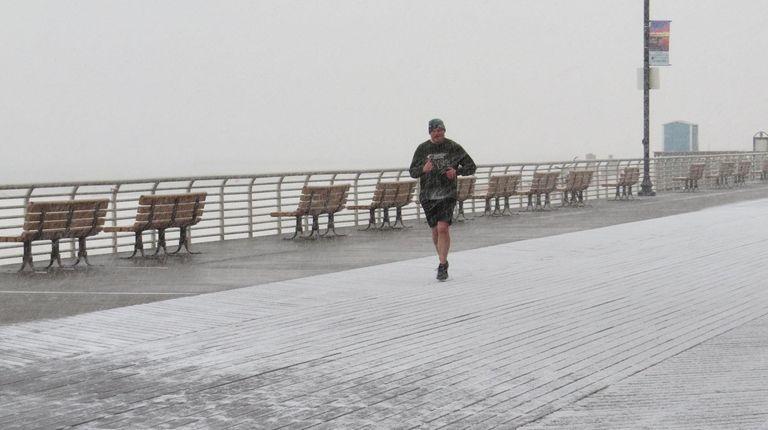 Snow falls on the Long Beach Boardwalk on