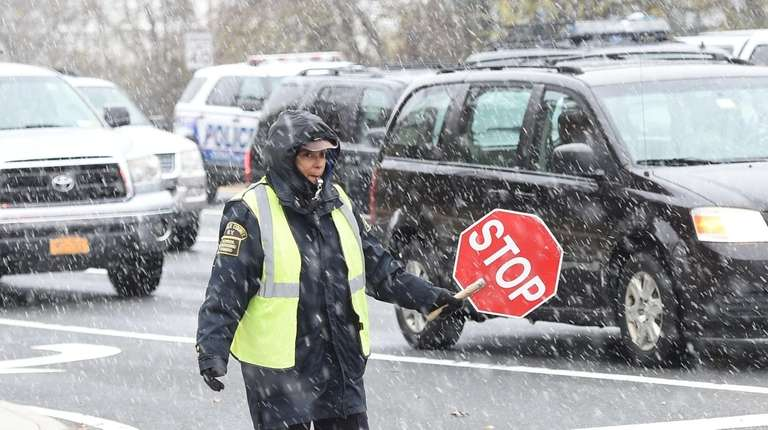 Crossing guard Mario Custodio, directs traffic at the