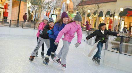 Skaters enjoy the outdoor ice skating rink at