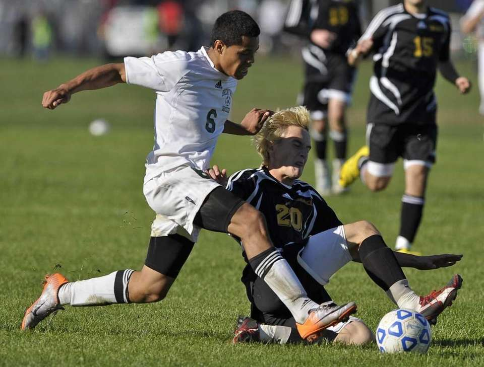 Commack's Josh Bacon slide tackles the ball from