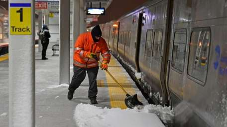 A worker clears snow off the Hicksville LIRR